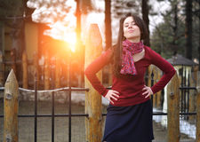 Beautiful stylish young woman in scarf red pullover posing alone against yard and sunset light. Hands on shoulders. Stock Photo