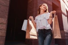 Beautiful stylish young woman with shopping bags walking on city street in summer. Happy and excited girl shopper. Sale royalty free stock photo