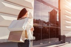 Beautiful stylish young woman with shopping bags walking on city street in summer. Happy girl holding purchases royalty free stock photos