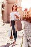 Beautiful stylish young woman with shopping bags walking on city street in summer. Sale stock image