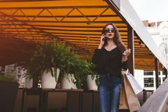 Beautiful stylish young woman with shopping bags walking out of cafe on city street and talking on phone. royalty free stock photo