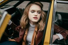 Beautiful stylish young woman sitting in old-fashioned car. And looking away stock photos