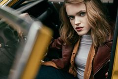 Beautiful stylish young woman sitting in old-fashioned car and looking. At camera royalty free stock photo