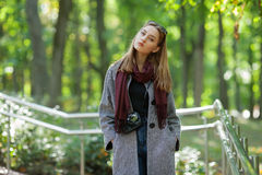 Beautiful stylish young woman in a warm scarf blue jeans trendy cozy coat walking along in fall city park Stock Images