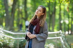 Beautiful stylish young woman in a warm scarf blue jeans trendy cozy coat walking along in fall city park Royalty Free Stock Photography