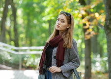 Beautiful stylish young woman in a warm scarf blue jeans trendy cozy coat walking along in fall city park Royalty Free Stock Images