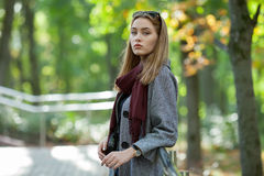Beautiful stylish young woman in a warm scarf blue jeans trendy cozy coat walking along in fall city park Stock Image