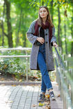 Beautiful stylish young woman in a warm scarf blue jeans trendy shoes and cozy coat walking along in fall city park Stock Photography