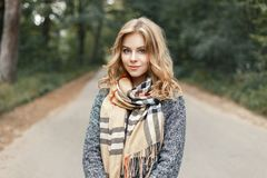 Beautiful stylish young woman in a warm scarf and coat walking royalty free stock photo