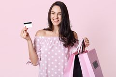 Beautiful stylish young woman wearing polka dot dress, holding shopping bags and credit card, stands smiling over pink background stock image