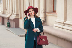 Beautiful stylishly dressed young woman smiling while talking on the phone outdoors. Beautiful stylishly dressed young woman smiling while talking on the phone Royalty Free Stock Photo