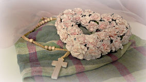 Beautiful subtle composition on the table. Heart pink flowers and a wooden cross on a checkered napkin Royalty Free Stock Photos