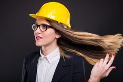 Beautiful successful architect girl waving her hair. In the air and posing on dark background stock photography