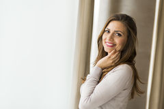 Beautiful and successful brunette  posing in front of a window Royalty Free Stock Photography