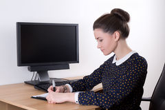 Beautiful successful business woman working in office and comput Stock Images