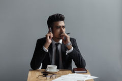 A beautiful successful man talking on phone office in cafe. Stock Image