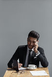 A beautiful successful man talking on phone office and writing in a notebook in cafe. Royalty Free Stock Photography