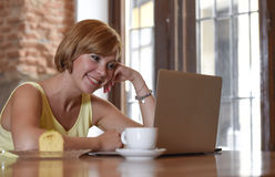 Beautiful successful woman working at coffee shop with laptop computer enjoying coffee cup Royalty Free Stock Image