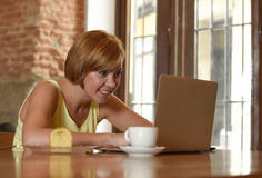 Beautiful successful woman working at coffee shop with laptop computer enjoying coffee cup Stock Images