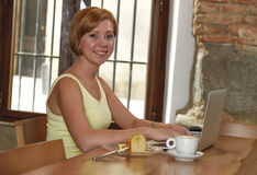 Beautiful successful woman working at coffee shop with laptop computer enjoying coffee cup Stock Photography