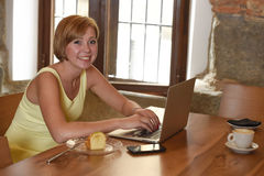 Beautiful successful woman working at coffee shop with laptop computer enjoying coffee cup Royalty Free Stock Photography