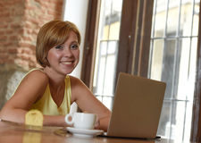 Beautiful successful woman working at coffee shop with laptop computer enjoying coffee cup Stock Photo