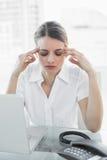 Beautiful suffering businesswoman having headache sitting at her desk Stock Photo