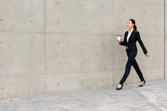 Beautiful suit woman holding white coffee cup. Beautiful suit right woman holding white coffee paper cup walking in office outside gray wall background walkway stock photos