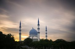 The beautiful Sultan Salahuddin Abdul Aziz Shah Mosque over stunning sunrise background. Soft focus due to long exposure shot Royalty Free Stock Photos