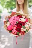 Beautiful summer bouquet. Arrangement with mix flowers. Young girl holding a flower arrangement with hydrangea. The. Concept of a flower shop stock photography