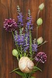 A beautiful summer bouquet, wildflowers, wild onions, Veronica long-leaved violet on a wooden background of black walnut. Minimalism. Beautiful summer stock image