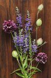 A beautiful summer bouquet, wildflowers, wild onions, Veronica long-leaved violet on a wooden background of black walnut. Minimalism. Beautiful summer stock photo