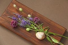 A beautiful summer bouquet, wildflowers, wild onions, Veronica long-leaved violet on a wooden background of black walnut. Minimalism. Beautiful summer royalty free stock photos
