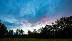 Beautiful summer colorful sunset over green meadow and forest Stock Photo