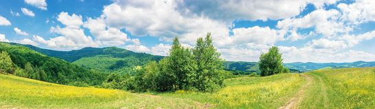 Beautiful summer countryside in mountains. Wonderful panoramic scenery on a sunny day. country road through rural fields. hills and mountains in the distance stock photo