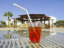 Beautiful summer day, a glass with a transparent red cocktail and a straw on a transparent table stock photos