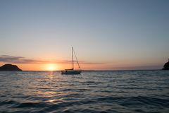Summer time Ocean sunset with Yacht royalty free stock images