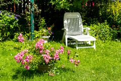 Beautiful summer garden with a white deckchair Royalty Free Stock Photography