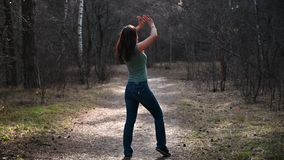 Beautiful summer girl in forest, standing in yoga pose on rug. Keeps balance, meditates, muscle stretching, outdoor. Gymnastics. Blue jeans, sportswear stock footage