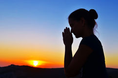 Beautiful summer Girl in prayer. Girl folded her hands in prayer. Beautiful sunset. Colorful sky. Tenderness and serenity Royalty Free Stock Image