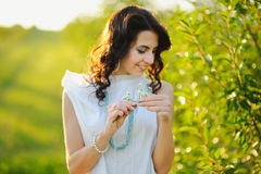 Beautiful summer girl with chamomile in hands Stock Photo