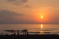 Beautiful summer golden sunset above.with calm waves and reflection of sun on the beach. A people on the beach and sea outdoors at Stock Photography