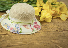 Beautiful summer hat and a bouquet of yellow tulips on a wooden table. stock images