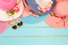 Beautiful summer hats with lady sunglasses on blue wooden backgr. Ound flat lay for summer background and design Royalty Free Stock Photos