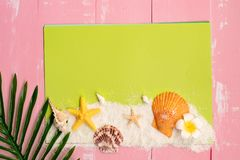 Beautiful summer holiday, Beach accessories, seashells, sand and palm leave on paper for copy space stock photography