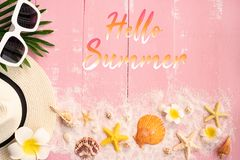 Beautiful summer holiday, Beach accessories, seashells, sand, hat, sunglasses and palm leave on wooden backgrounds royalty free stock image