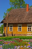 Beautiful Summer House in Countryside. Beautiful well maintained summer house in light brown color at European countryside with beautiful flower bed and green Stock Photography