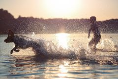 Free Beautiful Summer Landscape. A Kid Is Playing With A Dog In Lake. Water Splashes . Sunset. Happy Childhood. Bright Summer Scene. Stock Photo - 124417690