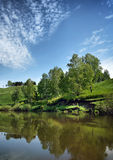 Beautiful summer landscape with calm little river and blue sky Stock Images