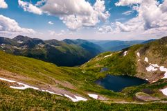 Beautiful summer landscape of Fagaras mountains. Stunning view from the top of a hill under the sky with clouds. lovely glacier on grassy slope over the deep Stock Image